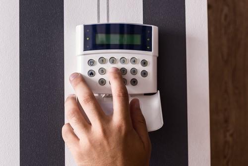 person pressing button on burglar alarm.